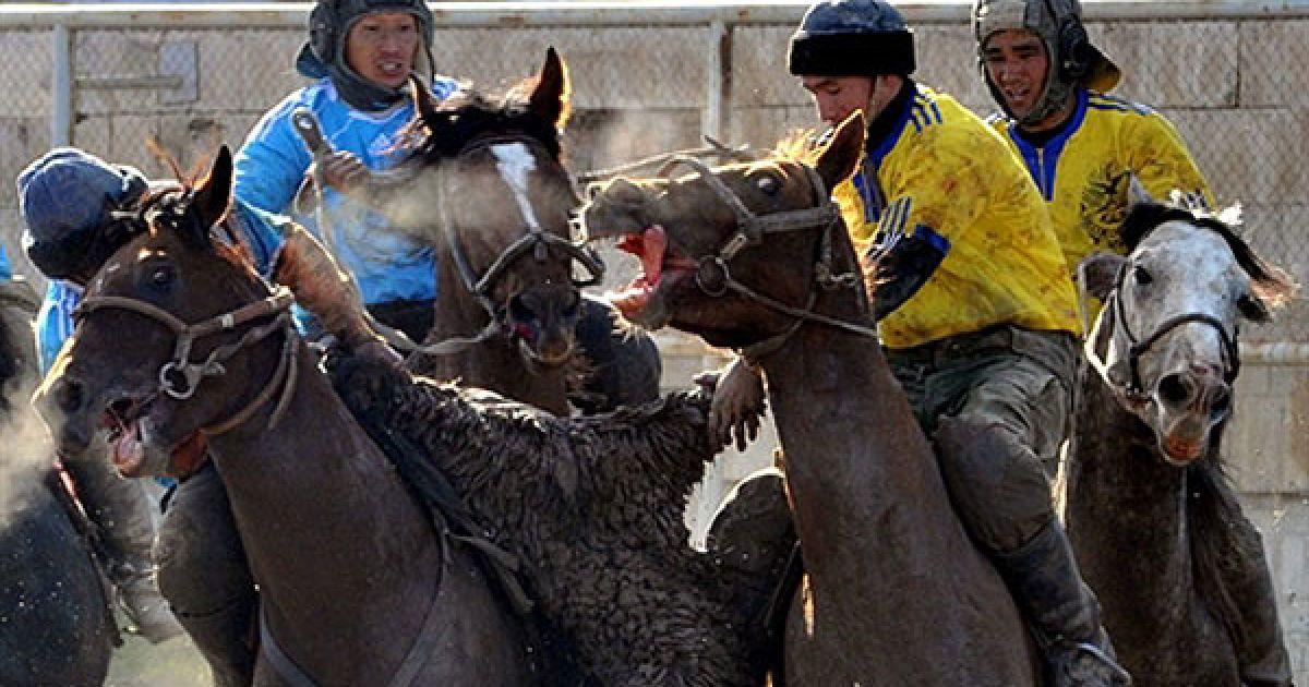 """Киргизстан, Бішкек. Киргизькі чоловіки грають у традиційний центральноазіатський вид """"спорту"""" — бузкаші, або кок-бору, у Бішкеку. Гравці на конях борються за очки, намагаючись закинути опудало цапа у колодязь. @ AFP"""