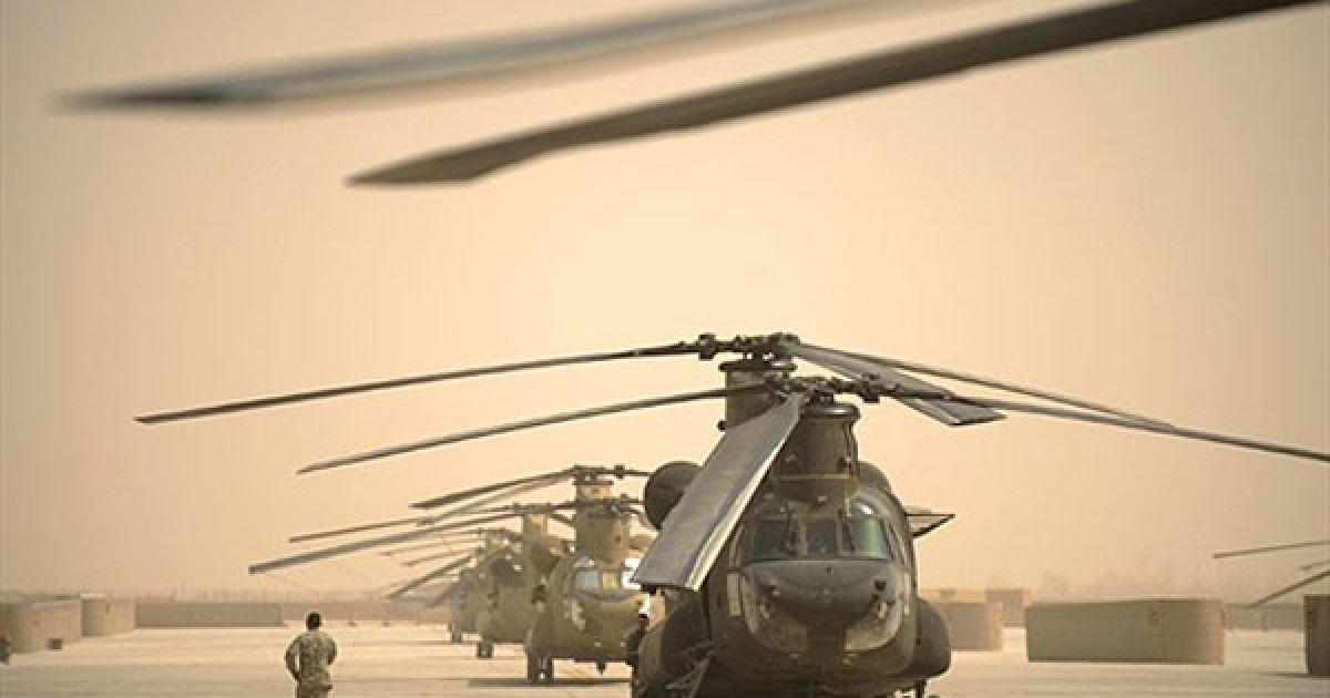 """Афганістан, Кандагар. Американський льотчик проходить повз гелікоптери """"Чінук"""" на авіабазі Кандагар. Коаліційні сили змогли зупинити талібів у деяких районах Афганістану. @ AFP"""