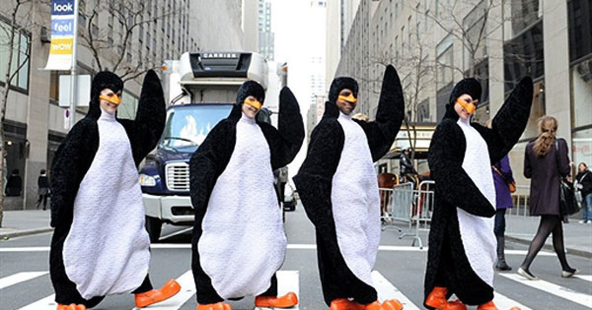 """США, Нью-Йорк. Актори у костюмах пінгвінів з мюзиклу """"Madagascar Live"""" переходять вулицю поруч із Рокфеллер-центром в Нью-Йорку. @ AFP"""