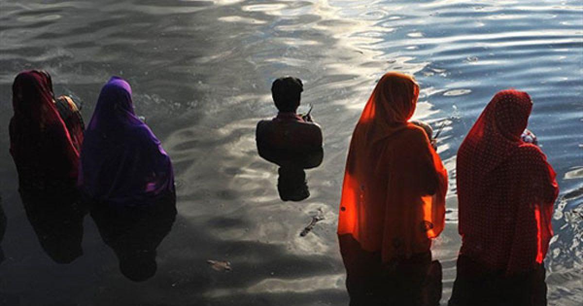 Індія, Бангалор. Індуїсти моляться Сонцю під час релігійного свята Chhath, стоячи у воді в Бангалорі. Свято Chhat присвячене Господу Сурья (Сонцю), Агні (вогню) і богу Картікея (Мурга). Люди моляться за благополуччя сім'ї, оскільки вважається, що бажання людей виповняться, якщо вони дотримуватимуться Пуджі. @ AFP