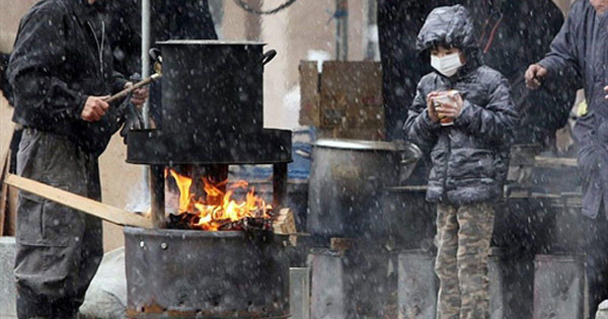 Японія, Сендай. Хлопчик чекає доки закипить вода, щоб зробити локшину швидкого приготування, на вулиці міста Сендай, префектура Міягі. У зруйнованій стихіями Японії влада нарахувала вже понад 4 тисячі загиблих. @ AFP
