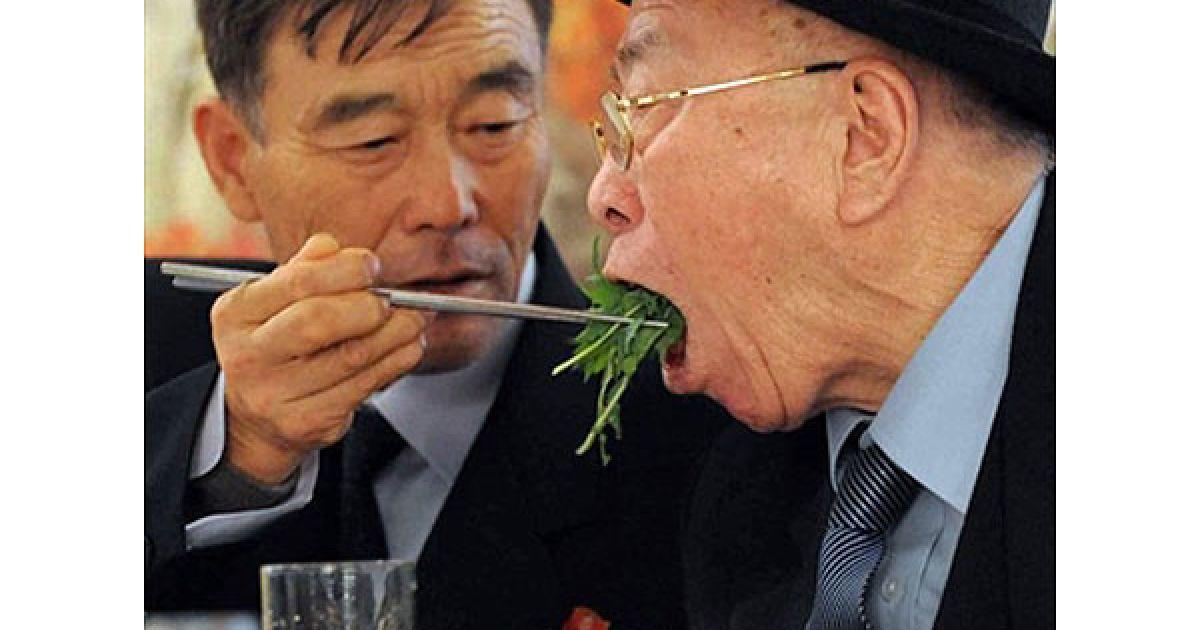 КНДР, гора Кимган. Північний кореєць Рю годує свого батька (з Південної Кореї) під час спільного обіду, який влаштували для розділених сімей у прикордонному місті поблизу гори Кимган у Північній Кореї. Південна і Північна Корея продовжують возз'єднувати сім'ї, розділені Корейською війною на шість десятиліть. @ AFP