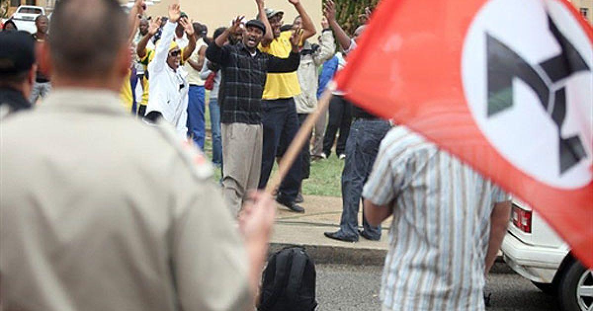 Південна Африка, Вентерсдорп. Члени правлячого Африканського національного конгресу співають під час зіткнення з прихильниками крайньо правої політичної організації і колишньої воєнізованої групи Африканерський руху опору (АРО). Групи зустрілись біля будівлі суду в місті Вентерсдорп, де почався судовий процес над 15-річним неповнолітнім, якому були пред'явлені звинувачення у забитті до смерті 69-річного лідера АРО Євгена Терібланша. Терібланш був забитий до смерті у своєму ліжку в квітні. Це вбивство потрясло країну, в якій досі зберігається расова напруженість через 16 років після закінчення апартеїду. @ AFP