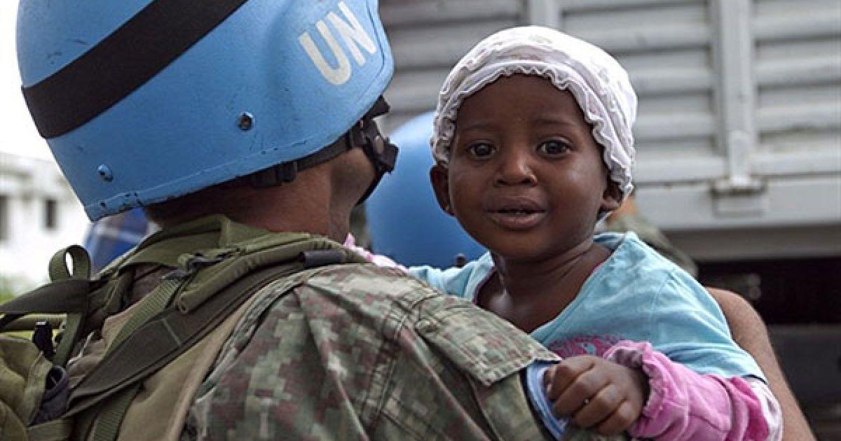 Гаїті, Порт-о-Пренс. Миротворець ООН тримає на руках дитину, доки її матір спускається з вантажівки ООН після прибуття до табору для інтернованих у Порт-о-Пренсі. Місія ООН у Гаїті займається евакуацією населення до більш безпечних місць, оскільки на країну насувається тропічний шторм Томас. @ AFP