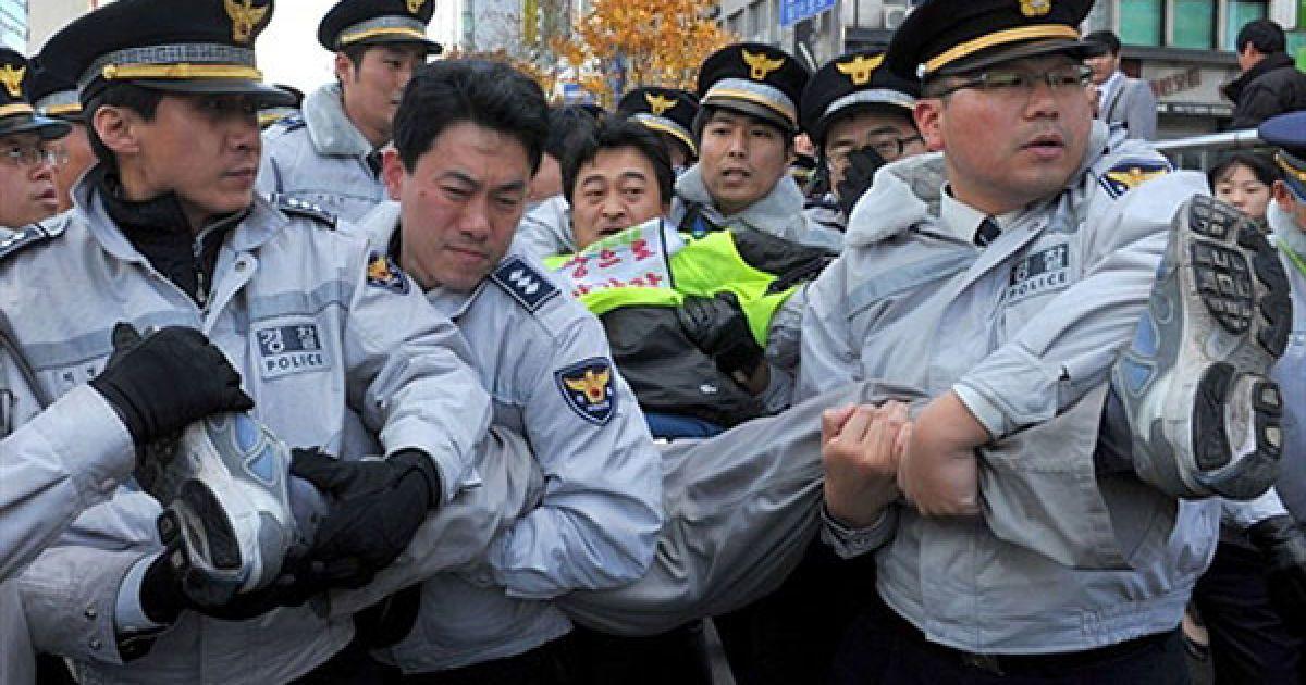 Республіка Корея, Сеул. Південнокорейська поліція затримує члена профспілки під час акції протесту біля готелю Ritz-Сarton у Сеулі, де 11 листопада розпочався дводенний саміт лідерів G20. @ AFP