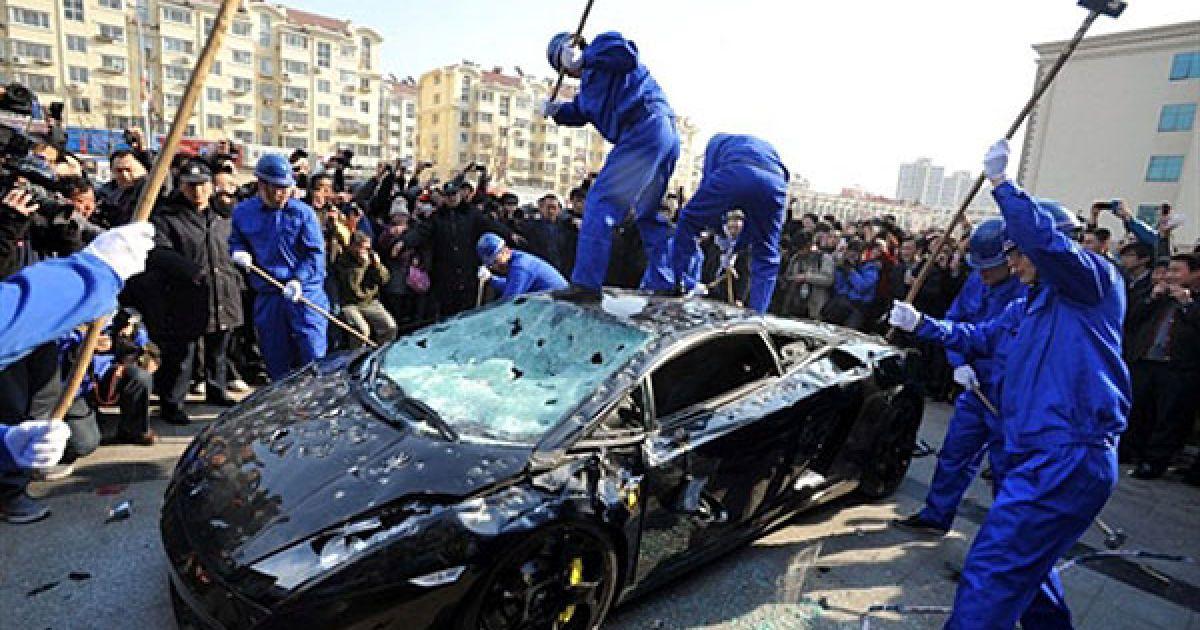 Китай, Циндао. У Всесвітній день захисту прав споживачів, власник розкішного спортивного автомобіля Lamborghini Gallardo L140 найняв людей, аби публічно знищити автомобіль, який перестав працювати після обслуговування на офіційній сервісній станції Lamborghini. @ AFP