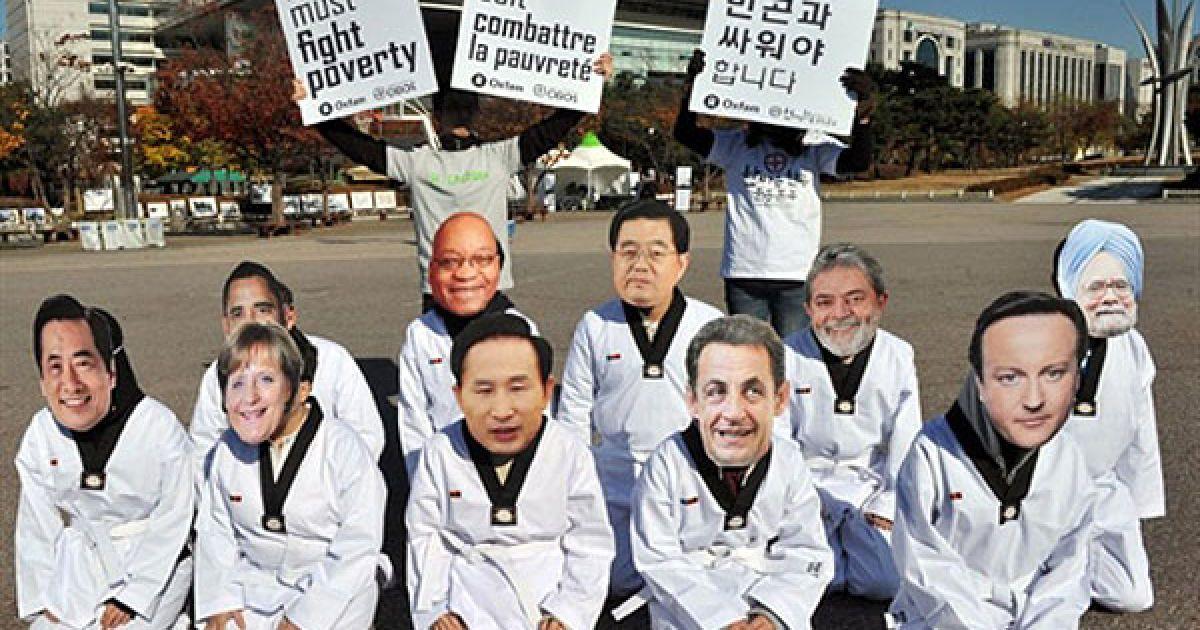 """Республіка Корея, Сеул. Активісти руху """"Oxfam"""" у масках із зображеннями облич лідерів країн G20 провели акцію протесту у сеульському парку напередодні саміту G20. 11 листопада світові лідери почнуть дводенні переговори на вищому рівні щодо відновлення рівноваги у світовій економіці. @ AFP"""