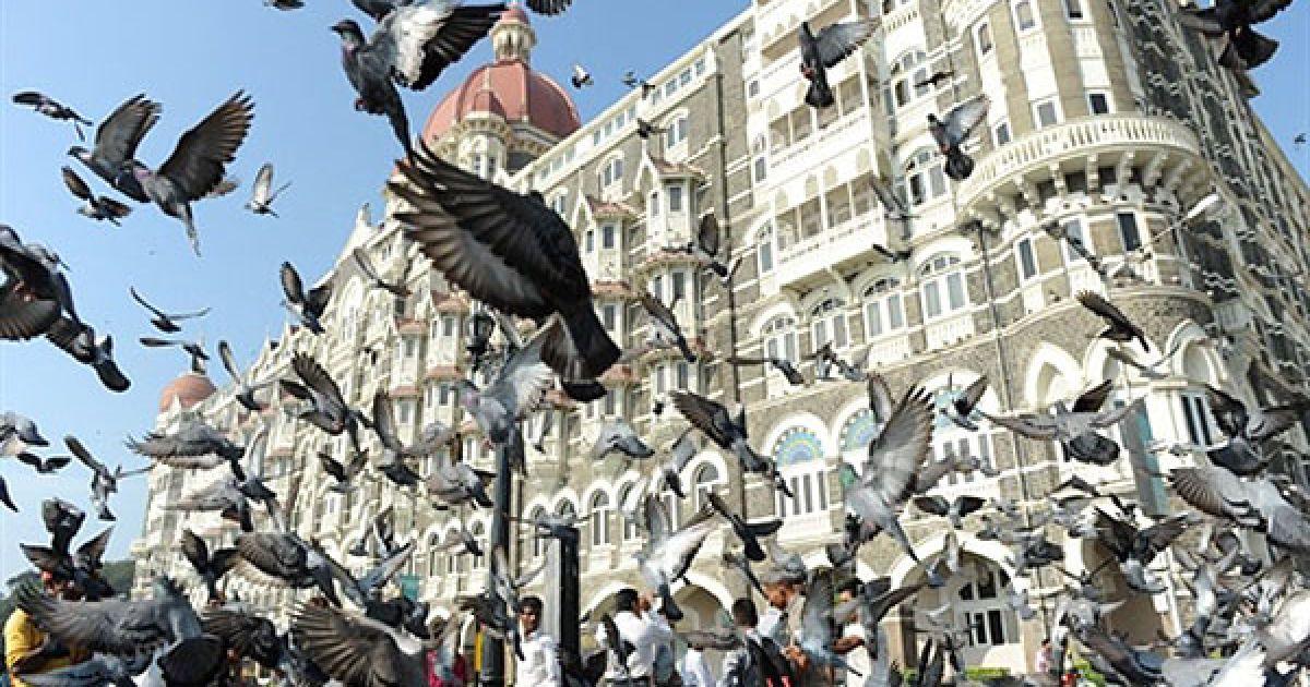 """Індія, Мумбаї. Туристи годують голубів біля Воріт Індії поблизу готелю """"Тадж-Махал Палас"""" у Мумбаї. @ AFP"""