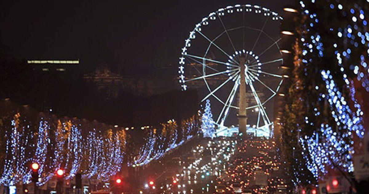 Франція, Париж. Різдвяні вогні освітлюють авеню на Єлисейських полях у Парижі. Мер Парижа Бертран Делано і французька актриса Мелані Лоран засвітили ці різдвяні вогні на знак початку підготовки до різдвяних свят. @ AFP