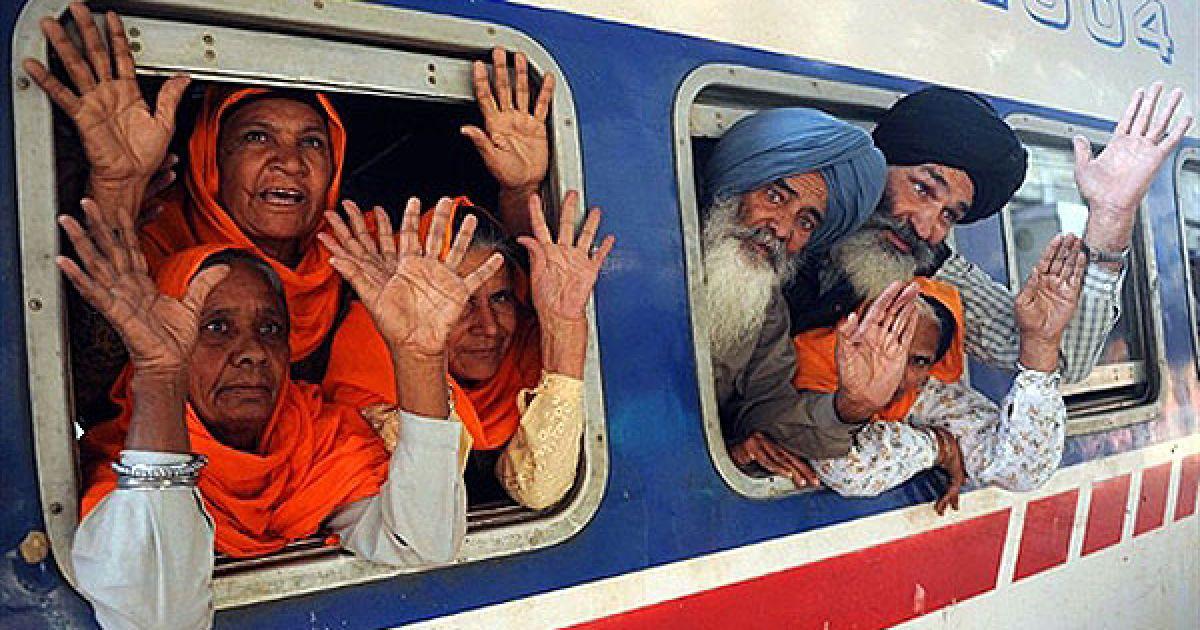 Індія, Амрітсар. Індійський сикхський паломник визирає з вагону поїзда, який прямує до Пакистану, на залізничній станції в Амрітсарі. Тисячі паломників-сикхів прямують з усього світу до Пакистану на святкування п'ятсот сорок першого дня народження Шрі Гуру Нанаки, який припадає на 21 листопада 2010 року. @ AFP