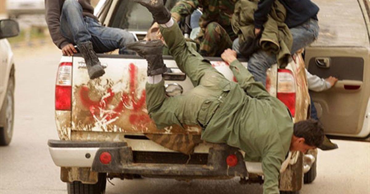 Лівійська Арабська Джамахірія, Бенгазі. Лівійський бойовик падає з вантажівки, коли повстанці залишають місто Бенгазі. Лівійські урядові війська напали на ключові міста, оточили повстанців і перерізали їм дорогу на північ. @ AFP