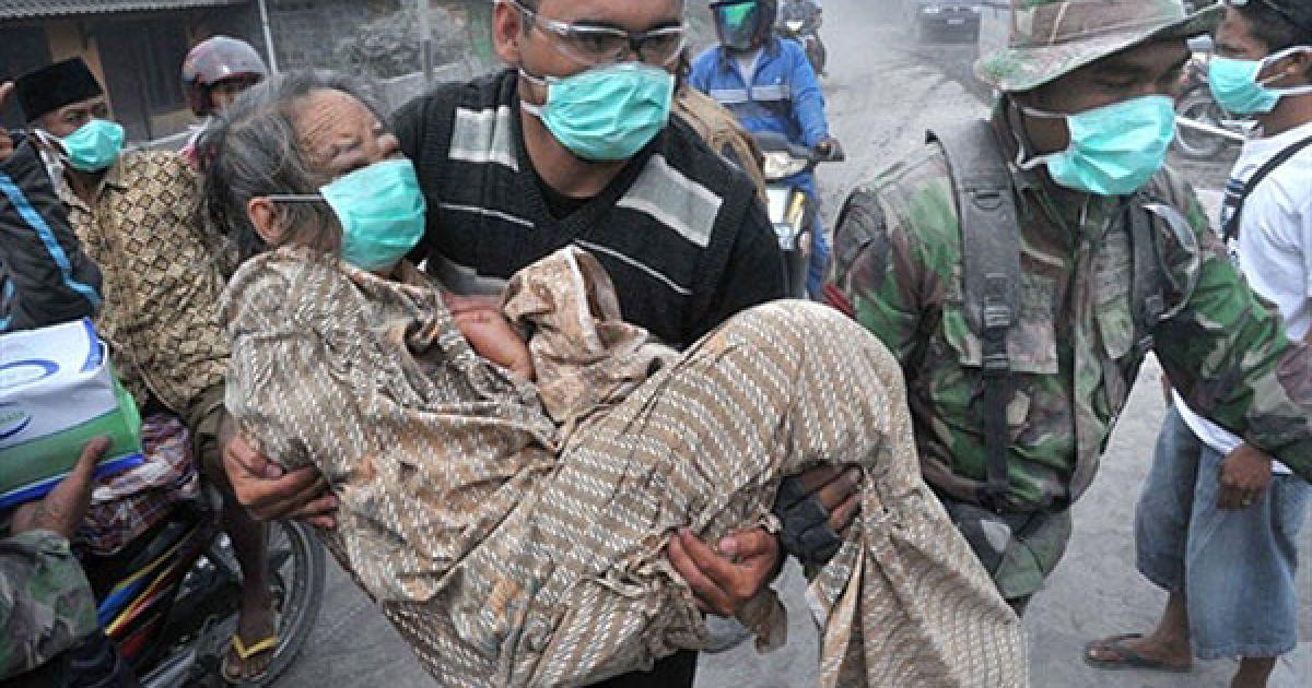Індонезія, Аргомуліо. Солдат і доброволець допомагають літній жінці у вкритому попелом селищі Аргомуліо на Центральній Яві. В результаті виверження найактивнішого вулкана Індонезії Мерапі, загинули щонайменше 69 осіб. Це виверження стало найбільшим за останні сто років. @ AFP