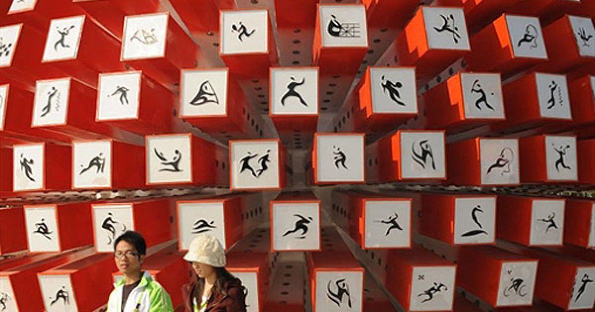 Китай, Гуанчжоу. Добровольці проходять повз стіну, на якій зображені значки із видами спортивних подій, які будуть проведені на 16-их Азіатських іграх в Гуанчжоу. Підготовка до Азіатських ігор тривала в Китаї протягом шести років, на організацію ігор було витрачено мільярди доларів інвестицій. @ AFP