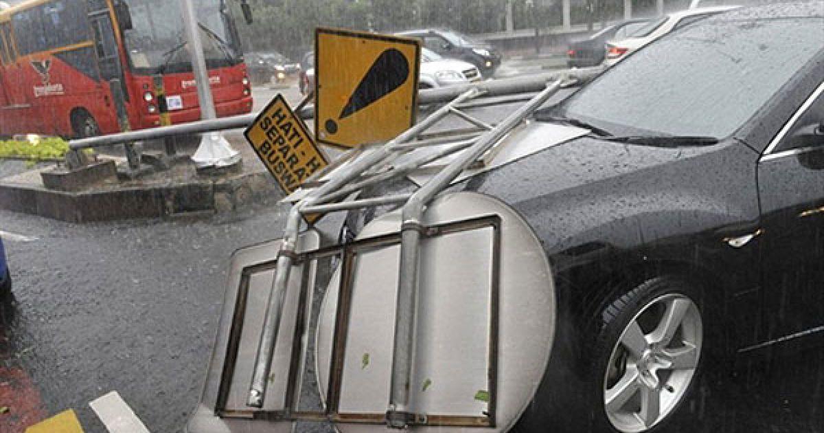 Індонезія, Джакарта. Поламаний дорожній знак лежить на капоті автомобіля на головній вулиці Джакарті під час сильної зливи. Через потужні дощі були затоплені кілька вулиць індонезійської столиці, утворились завали. @ AFP