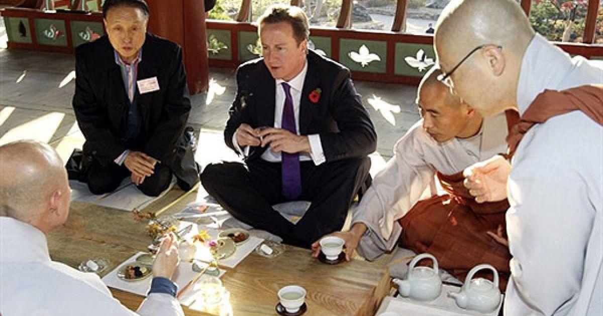 Республіка Корея, Сеул. Британський прем'єр-міністр Девід Камерон розмовляє з ченцями храму Бонгеун під час чайної церемонії в Сеулі. Лідери G20 провели другий день переговорів з питань врегулювання стану світової економіки. @ AFP
