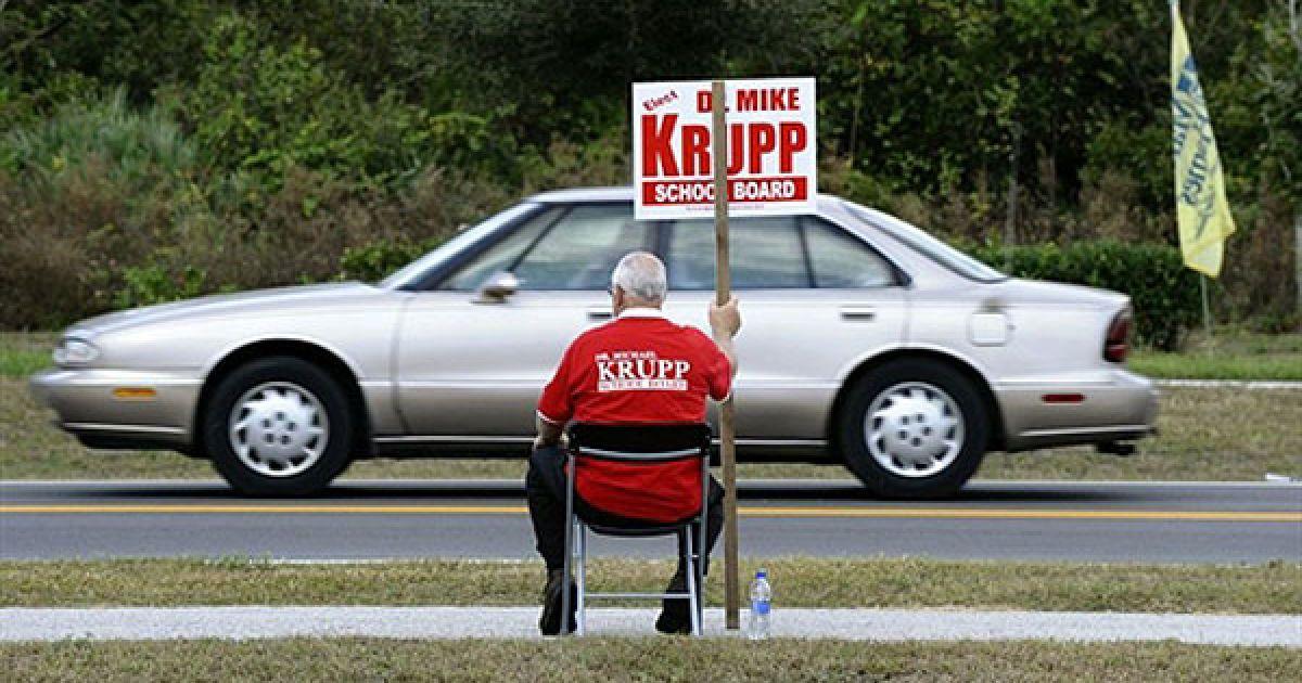 США, Тітусвілле. Доброволець тримає агітаційний плакат, сидячи поруч із виборчою дільницею у місті Тітусвілле, штат Флорида. У США почалось голосування на проміжних виборах. @ AFP