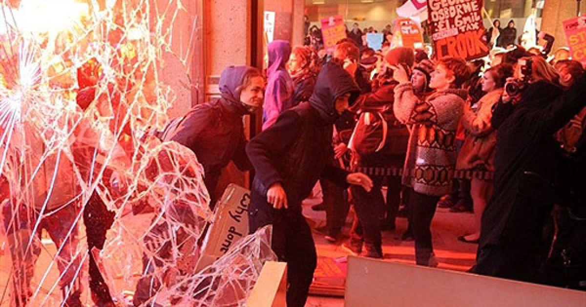 """Великобританія, Лондон. Демонстранти у світлі від спалахів через розбите вікно заходять до будівлі """"30 Мілбанк"""" під час маршу протесту студентів у центрі Лондона. Студенти провели гучну акцію протесту проти планів британського уряду втричі збільшити плату за навчання. Студенти увірвалися до штаб-квартири партії прем'єр-міністра Девіда Камерона біля будівлі парламенту. @ AFP"""