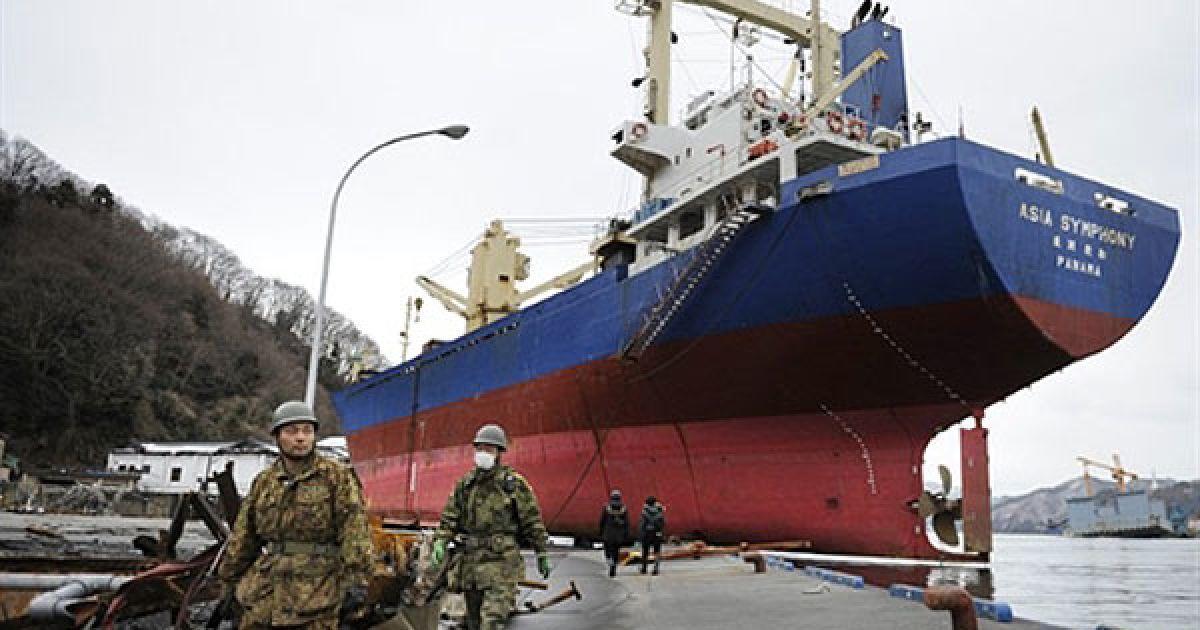 """Японія, Камаісі. Люди проходять повз 4724-тонний вантажний корабель """"M.V. Asia Symphony"""", який викинуло на пристань під час руйнівного цунамі в порту міста Камаісі. Всі члени екіпажу врятовані та отримали тимчасове житло. @ AFP"""