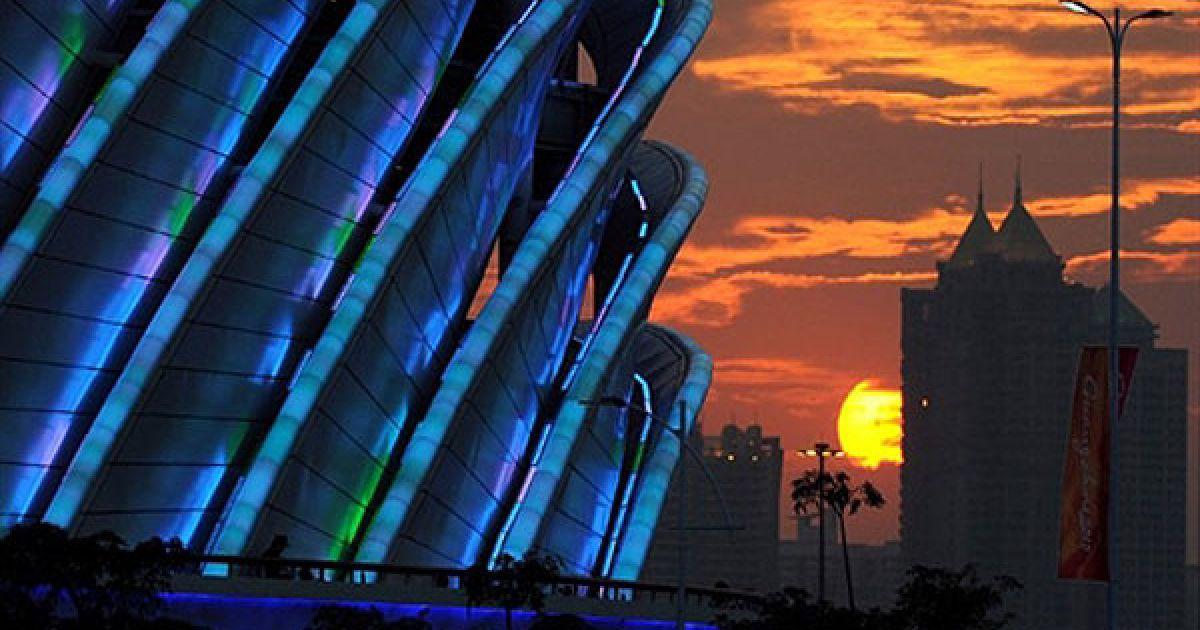 Китай, Гуанчжоу. Сонце сідає за стадіон Haixinsha незадовго до початку урочистої церемонії відкриття 16-их Азіатських ігор в Гуанчжоу. Спортсмени з 45 країн змагатимуться у 42 спортивних дисциплінах. @ AFP