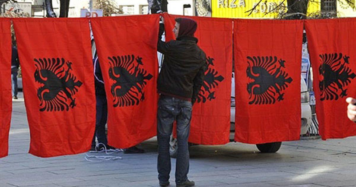 Сербія, Пріштіна. Чоловік, косовський албанець, продає албанські прапори у місті Пріштіна. 1 грудня у Косово почалась 10-денна кампанія підготовки до перших загальних виборів. Країна оголосила про свою незалежність, і ці вибори стануть серйозним випробуванням політичної зрілості нової країни. Двома основними претендентами на перемогу є Демократична партія Косово і Демократична ліга Косова під керівництвом Тачі і Іси Мустафи, відповідно. @ AFP