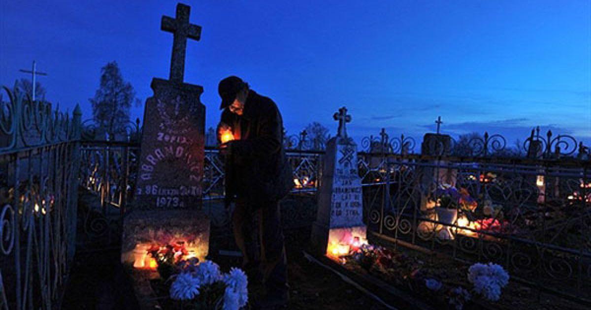 Білорусь, Борунов. Чоловік ставить свічки на могилу на цвинтарі біля білоруського села Борунов на честь свята Дзяди (Дня пам'яті). @ AFP