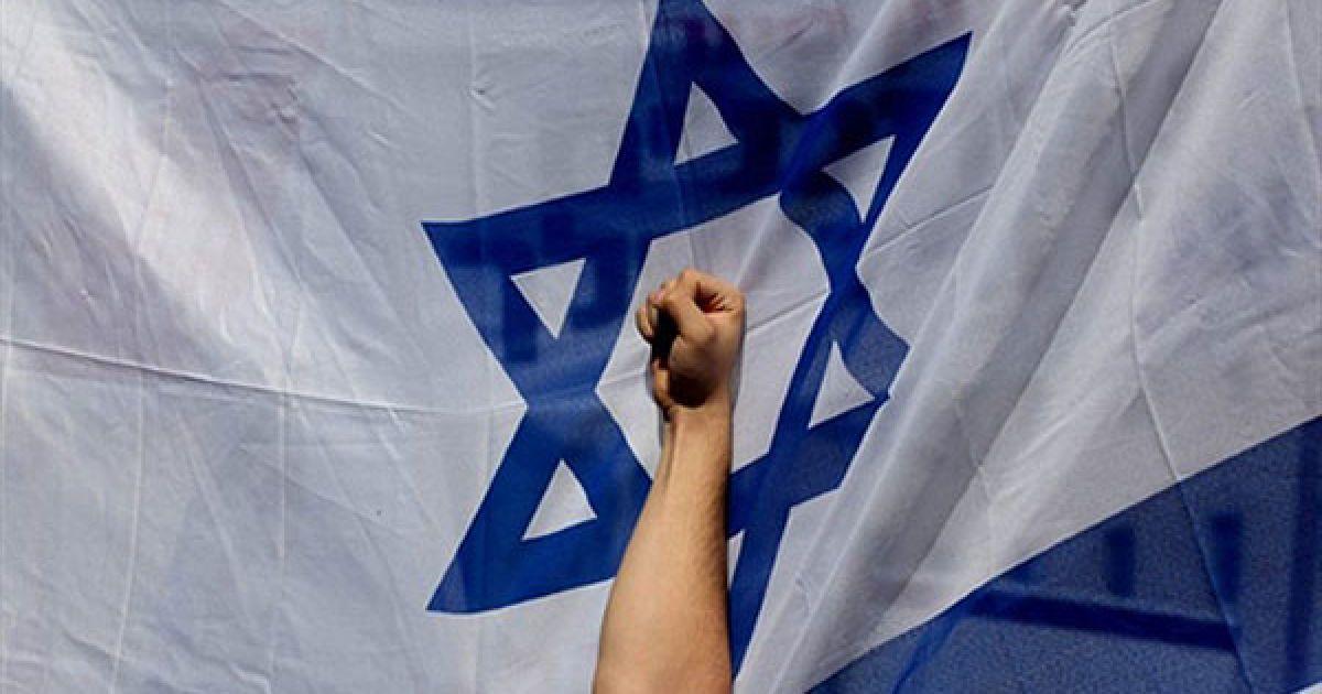 Єрусалим. Кулак учасника акції протесту на тлі ізраїльського прапору. Тисячі ізраїльських поселенців, в основному школярі, провели акцію протесту перед будівлею уряду в Єрусалимі з вимогами заморозити втілення плану врегулювання конфлікту. @ AFP