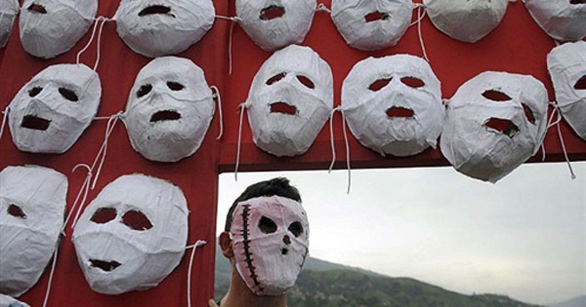 Колумбія, Медельїн. Людина у масці тримає хрест на Ла Ескомбрера, звалищі для будівельних матеріалів, на околиці Медельїну, департамент Антіокия, Колумбія. За словами місцевих жителів, близько 160 чоловік були вбиті і поховані воєнізованими колумбійськими партизанами на цьому звалищі. @ AFP