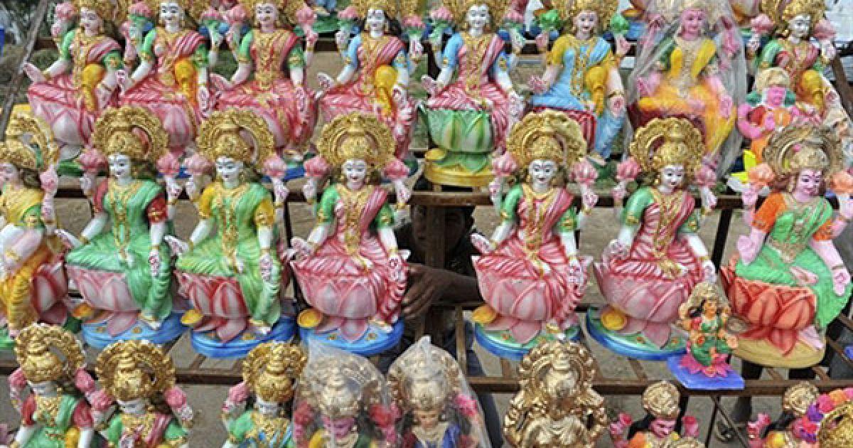 Індія, Хайдарабад. Індійський працівник поправляє статуї індуїстської богині Лакшмі, яка символізує гроші та багатство, виставлені у придорожньому кіоску в Хайдарабаді. В Індії відзначають свято вогнів Дівалі. @ AFP