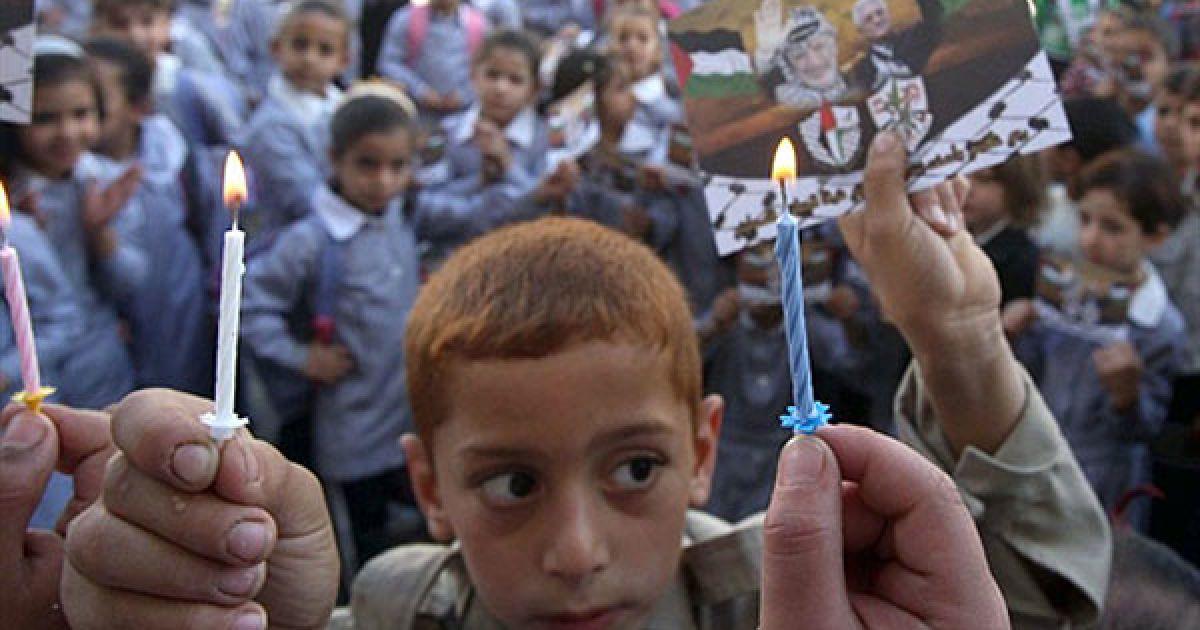Наблус. Школяр тримає фотографії покійного лідера Ясіра Арафата і його наступника Махмуда Аббаса під час церемонії з нагоди шостої річниці смерті Арафата у місті Наблус на Західному березі. @ AFP