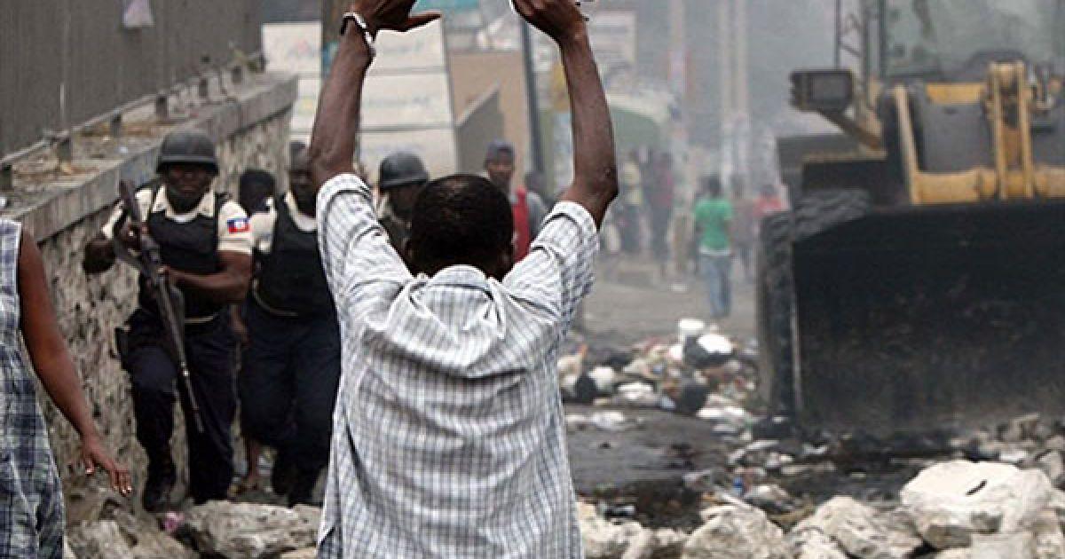 Гаїті, Порт-о-Пренс. Гаїтянин піднімає руки, доки він наближається до поліцейських. Бульдозер із поліцейським супроводом, призначений для очищення міста Порт-о-Пренс, було виведено на вулиці, заблоковані демонстрантами. Учасники акції протесту виступають проти результатів виборів у країні. Виборча комісія Гаїті наказала переглянути результати голосування, оскільки демонстрації переросли у насильницькі дії в кількох великих містах. @ AFP