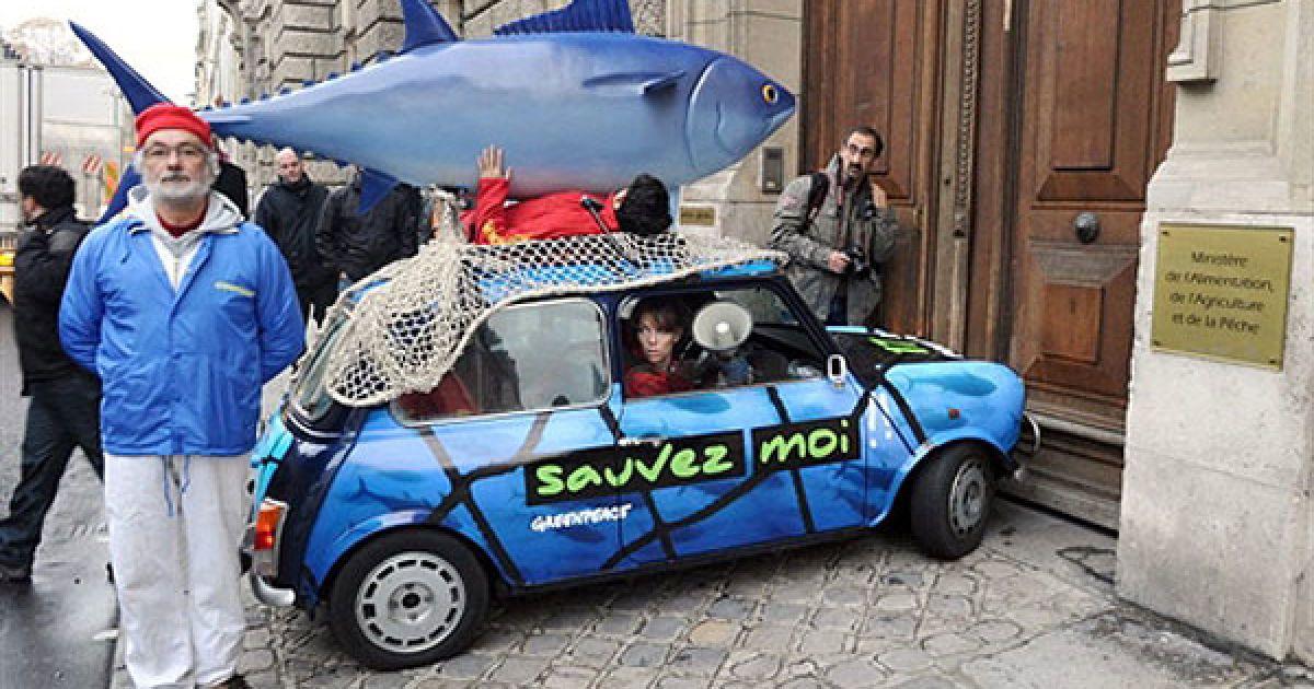 """Франція, Париж. Активісти руху """"Грінпіс"""" заблокували міністра риболовлі і сільського господарства Франції у Парижі. На машині з фігурою блакитного тунця на даху і плакатом """"Допоможи мені"""" вони виступили проти позиції Франції з питання вилову блакитного тунця. @ AFP"""