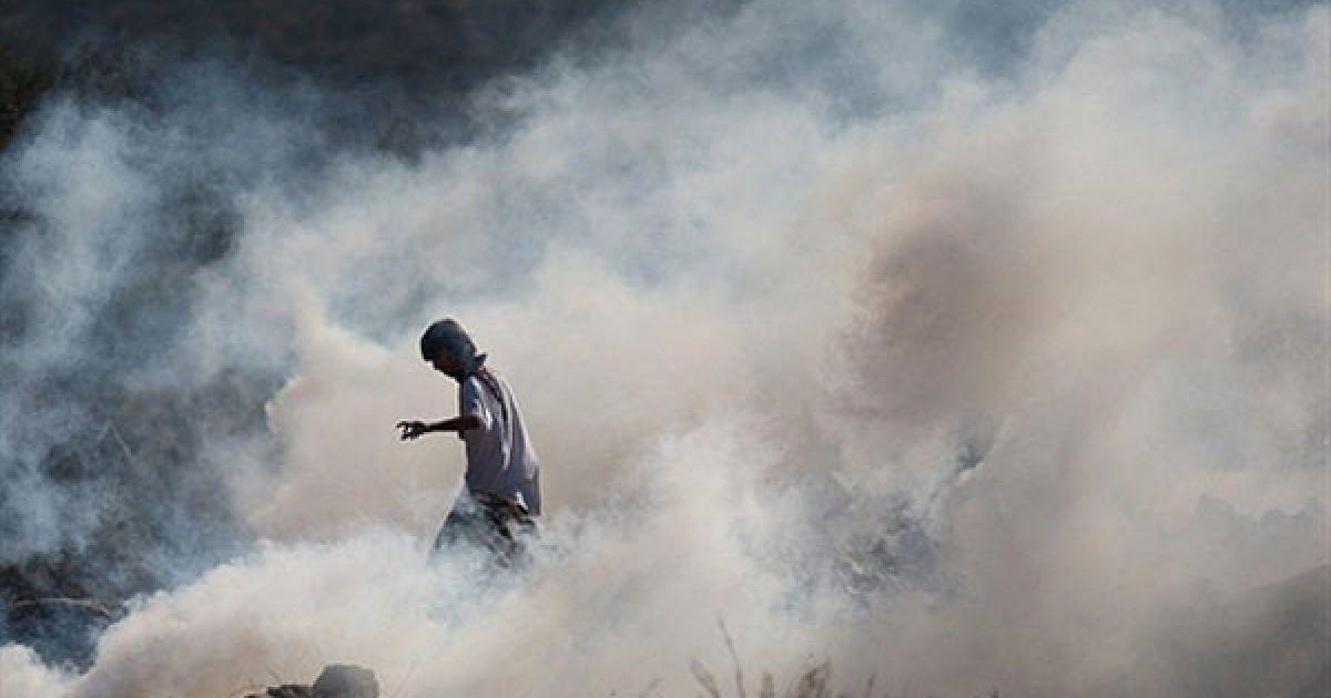 Білин. Палестинець у масці кидає каміння, стоячи у хмарі сльозогінного газу під час зіткнень з ізраїльськими солдатами, які відбулись на щотижневій демонстрації проти розділового бар'єру Ізраїлю у селі Білин поблизу Рамалли. @ AFP