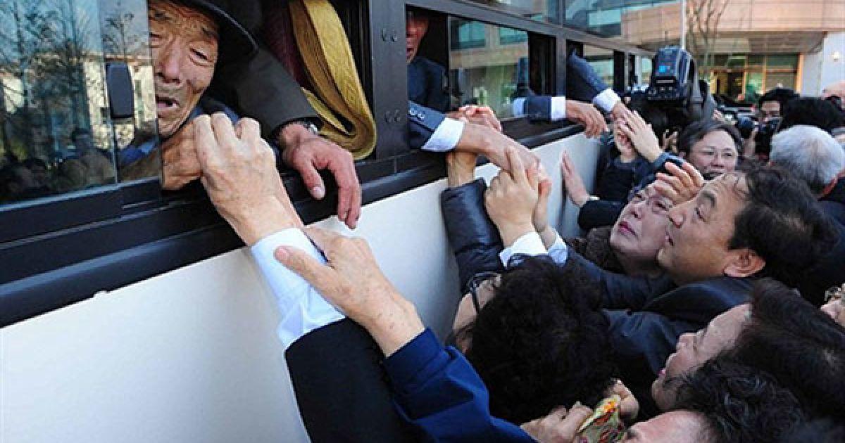 КНДР, гора Кимган. Північнокорейці (в автобусі) хапають за руки своїх південнокорейських родичів під час прощання після триденної зустрічі розділених сімей, яку провели на горі Кимган у Північній Кореї, неподалік від кордону. Сотні жителів Південної Кореї отримали можливість зустрітися зі своїми північнокорейськими родичами, з якими їх розділили після закінчення Корейської війни. @ AFP