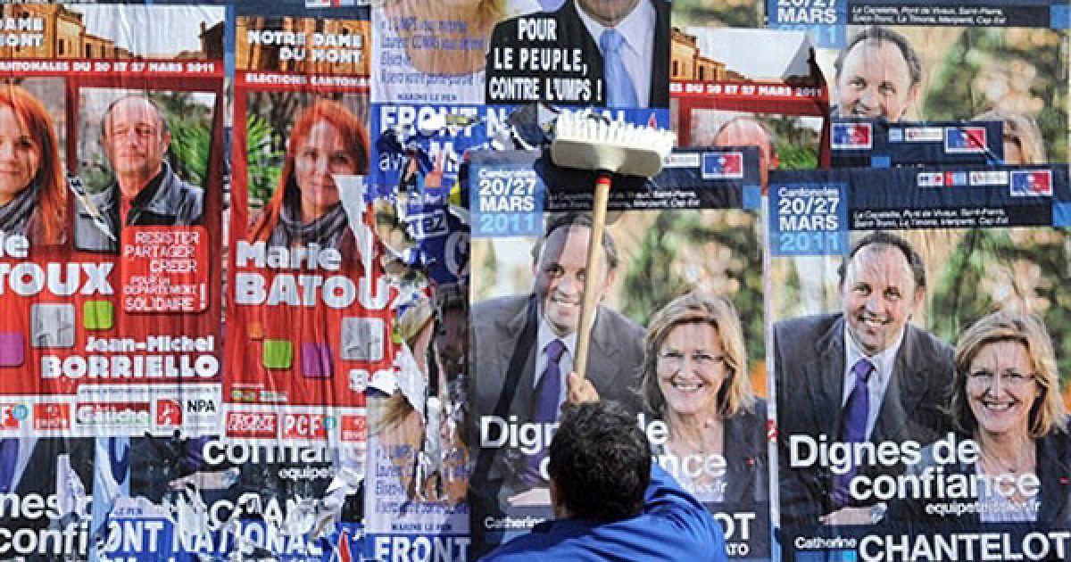 Франція, Марсель. Чоловік розвішує виборчі плакати у Марселі напередодні проведення місцевих виборів 20 і 27 березня. @ AFP