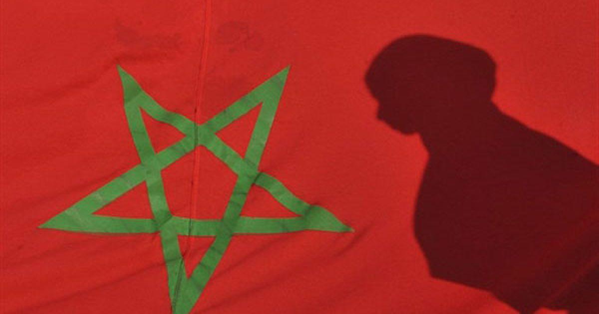 """Марокко, Рабат. Тінь молодої жінки відбивається на марокканському прапорі під час демонстрації у Рабаті, яку провели на честь 35-річчя """"Зеленого маршу"""". У листопаді 1975 року марокканський король Хасан II закликав 350 тисяч марокканців, """"озброєних"""" Кораном і національними прапорами, вирушити до кордону із Західною Сахарою, щоб підтримати незалежність колишньої іспанської колонії. Колишня іспанська колонія, Західна Сахара, була анексована Марокко у 1975 році. @ AFP"""