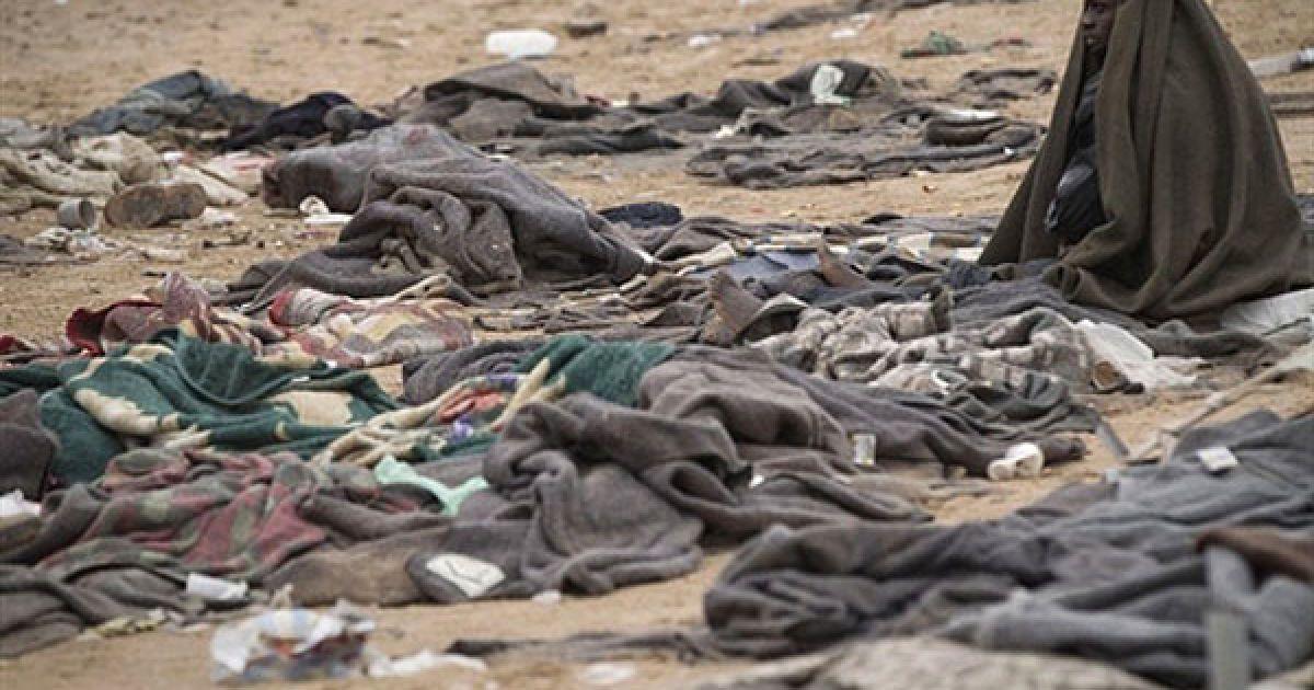 Туніс. Біженець з Гани, який утік з Лівії, захищає себе від дощу у таборі біженців, доки він чекає автобус до аеропорту Джерба. ООН заявила, що вже понад 250 тисяч осіб втекли з Лівії до сусідніх країни через заворушення та збройні конфлікти. @ AFP