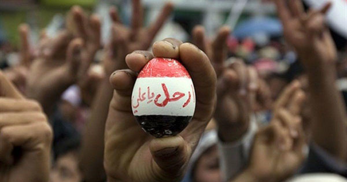 """Ємен, Сана. Антиурядовий єменський демонстрант тримає яйце, пофарбоване у кольори національного прапора із написом арабською """"Йди, Алі"""" під час мітингу з вимогою покласти кінець правлінню президента Алі Абдалли Салеха. @ AFP"""