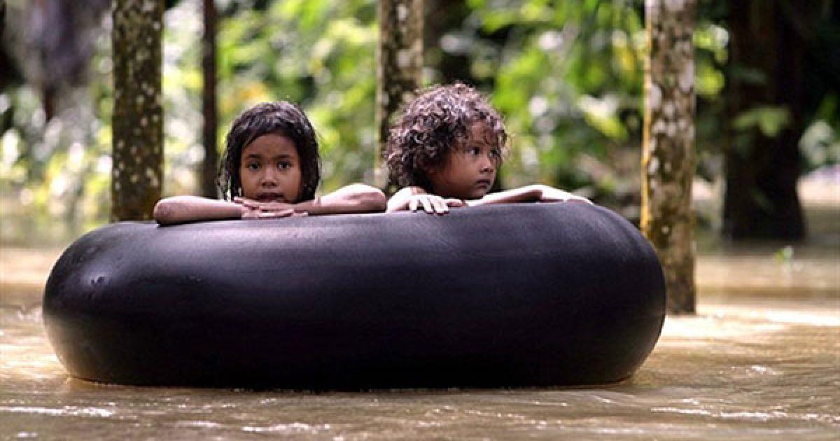 Таїланд, Наратхіват. Тайські діти пливуть на гумовому кільці через затоплене місто. Сильні дощі спричинили повінь у південній провінції Таїланду Наратхіват. Рятувальні служби змогли врятувати тисячі людей, які опинились у пастках всередині своїх будинків. В результаті повені, більше 100 чоловік по всій країні загинули. @ AFP