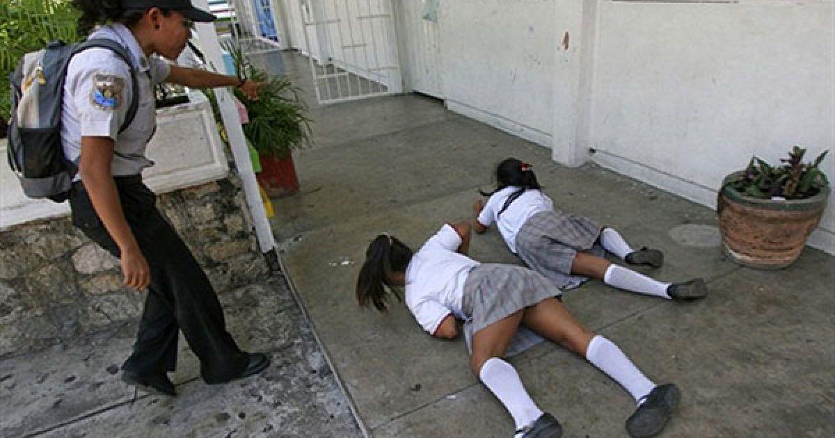 Мексика, Акапулько. Жінка-поліцейський дає вказівки учням початкової школи під час інсценування стрілянини у школі Феліпе Каррільо Пуерто в Акапулько. Департамент громадської безпеки проводить навчання з учнями, батьками і вчителями у державних і приватних школах штату Герреро, як превентивні заходи проти можливих насильницьких дій. @ AFP