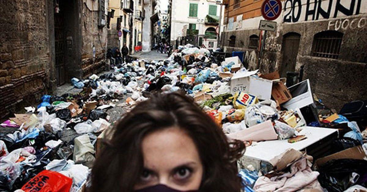 Італія, Неаполь. Жінка прикриває обличчя, доки вона йде вулицею, заваленою незібраним сміттям, у історичному районі міста Неаполь. Смердючі купи сміття накопичуються на вулицях Неаполя, наразі загальний обсяг незібраних відходів у місті досягає 3600 тонн. @ AFP