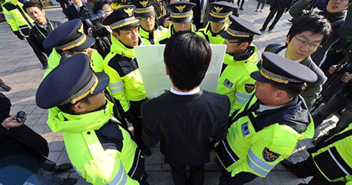 Республіка Корея, Сеул. Південнокорейського демонстранта оточили співробітники поліції під час його самотньої акції протесту проти одного з урядових проектів перед місцем проведення саміту G20 у Сеулі. @ AFP
