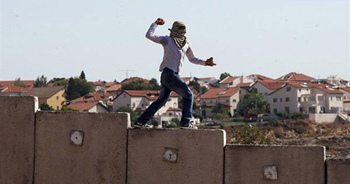 Нілін. Палестинець стоїть на вершині розділового бар'єру між Палестиною та Ізраїлем і кидає каміння у ізраїльських солдат під час щотижневого протесту у селищі Нілін на Західному березі. @ AFP