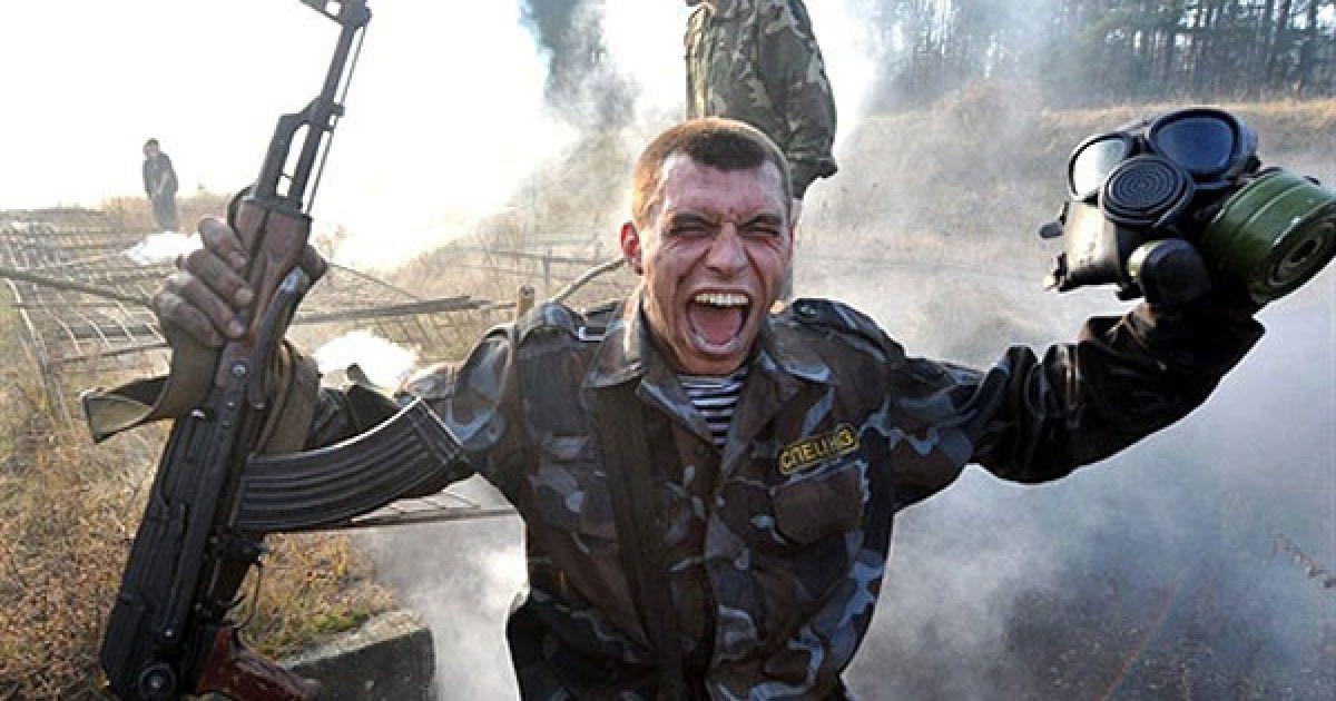 """Білорусь, Мінськ. Співробітник МВС Білорусі кричить, доки він проходить через хмару диму на смузі перешкод під час фізичного іспиту на """"краповий берет"""", який відбувся під Мінськом у Воловщині. Солдати, які проходять іспити, отримують берет бордового кольору і стають членами спеціальних сил. @ AFP"""