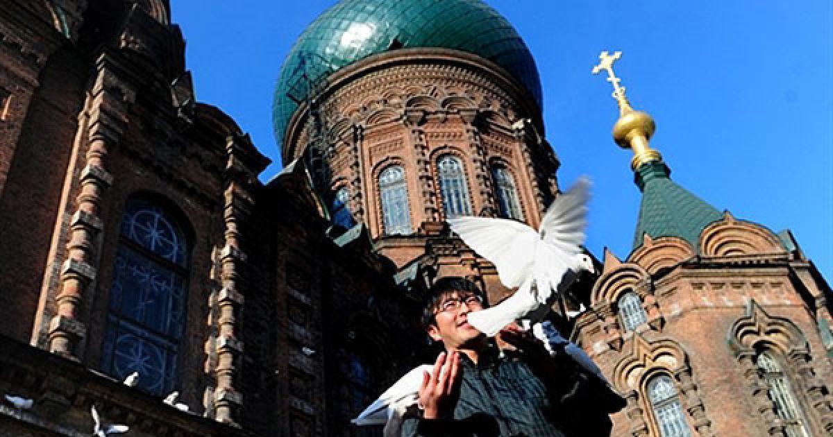 Китай, Харбін. Людина годує голубів перед Софійським собором у Харбіні. Собор був побудований у 1907 році після завершення Транс-Сибірської залізниці. @ AFP