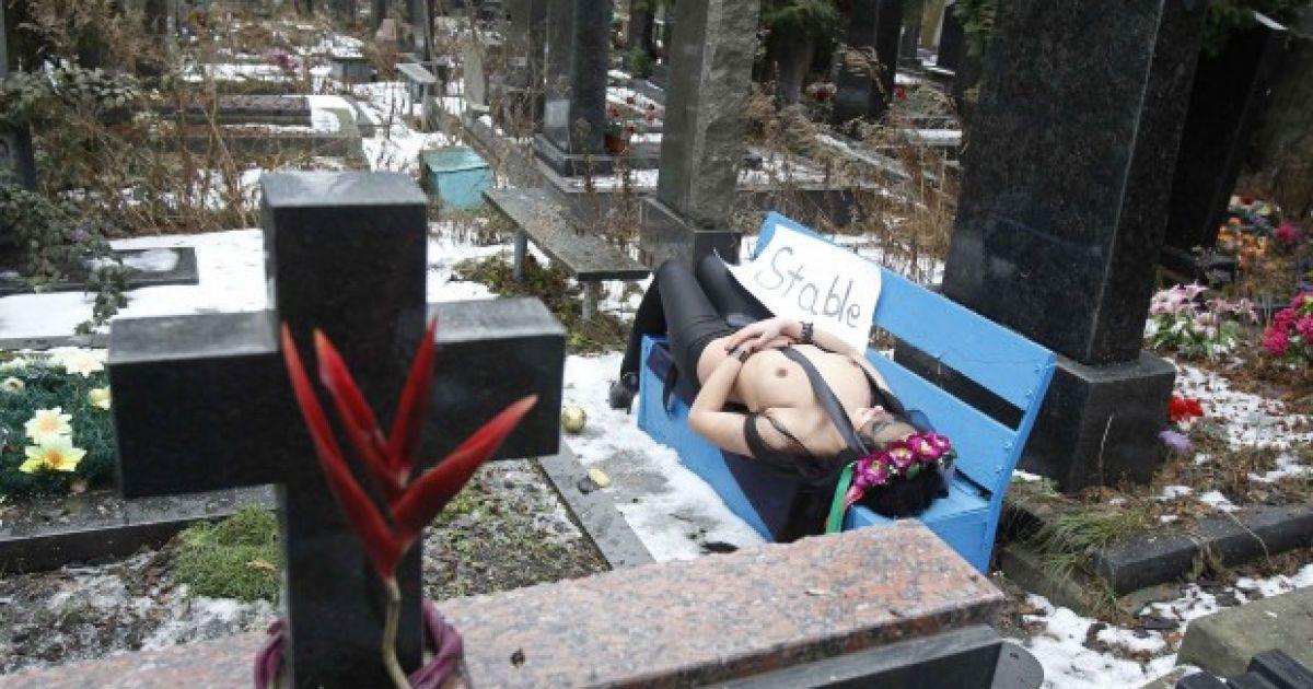 """Одна з активісток руху FEMEN роздяглась на кладовищі на знак протесту проти """"немовби стабільної"""" політики президента України Віктора Януковича. @ AFP"""