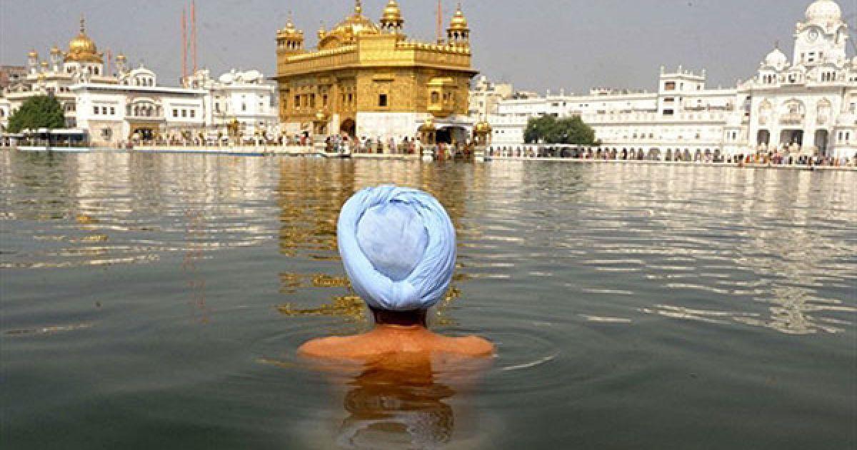 Індія, Амрітсар. Індійський сикх занурюється у святу купель перед Золотим Храмом у Амрітсарі. В Індії почались святкування Дівалі. @ AFP