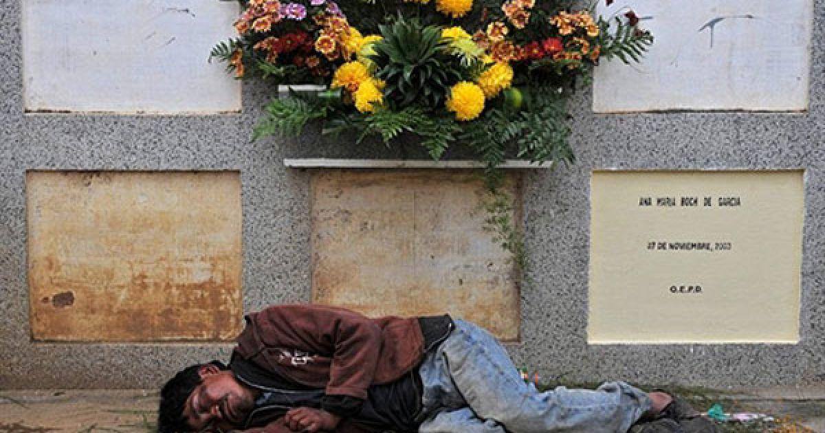 Гватемала, Сакатепекес. П'яний лежить біля могили, яку він прикрашав, на муніципальному цвинтарі Сан-Хуан у місті Сакатепекес. У світі відзначили День усіх святих — свято, коли християни згадують своїх померлих рідних і близьких. @ AFP