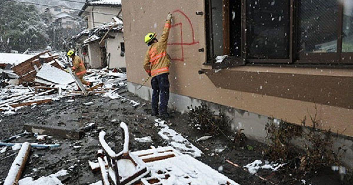 Японія, Камаісі. Член американської пошуково-рятувальні команди Фейрфакс з Вірджинії помічає будинок, щоб показати, що будинок обшукали і не знайшли там жодних жертв землетрусу. @ AFP