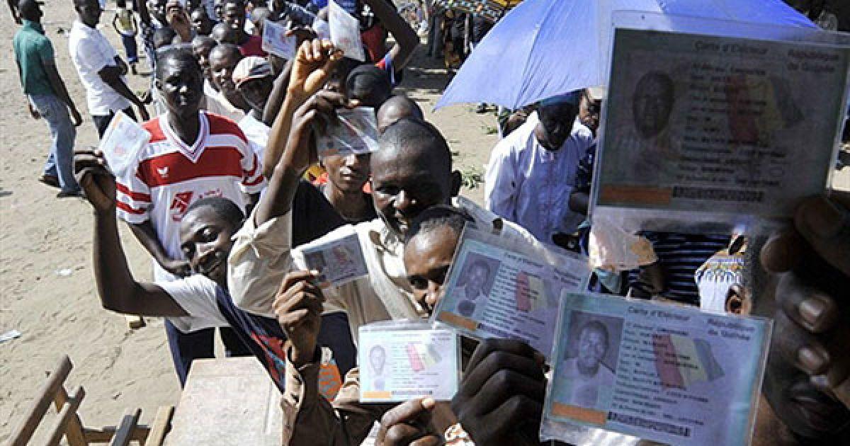 Кот-д'Івуар, Абіджан. Гвінейські жителі Кот-д'Івуара показують свої виборчі карти, доки вони стоять у черзі на виборчу дільницю в Абіджані. @ AFP