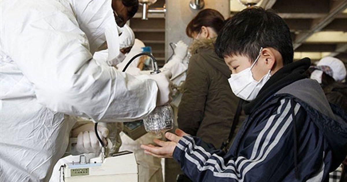 """Японія, Коріяма. Людина у костюмі радіаційного захисту сканує евакуйованого хлопчика лічильником Гейгера, щоб перевірити рівень радіації. На АЕС """"Фукусіма-1"""" військові скасували операцію з охолодження реактора через високий радіаційний фон. @ AFP"""